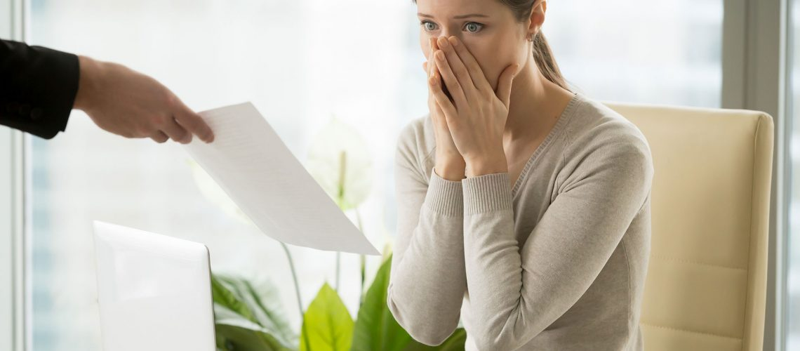 Young woman shocked when receiving dismissal notification from boss. Upset female employee worrying because of mistakes in calculations. Office worker can not believe in breaking employment contract