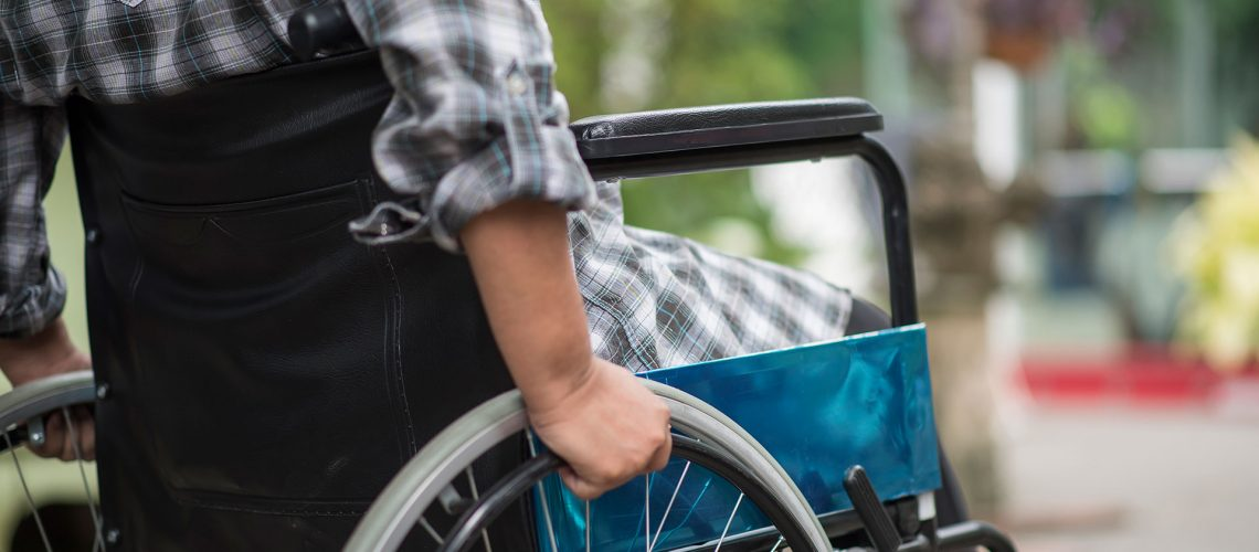 Close-up of senior woman hand on wheel of wheelchair during walk in hospital