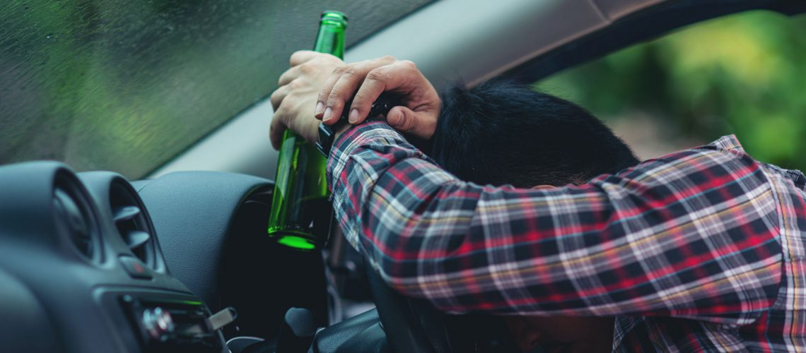 Hansome man holding beer bottle while driving a car