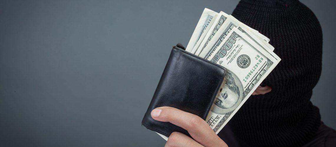 Black criminals wear a head yarn, hold a dollar card on a gray background.