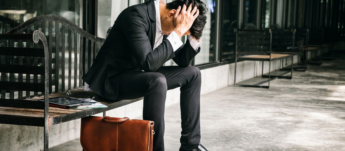 Concept of business failure and unemployment problem.An unemployed businessman sits alone in the corridor of an office. Is stressed about the future.