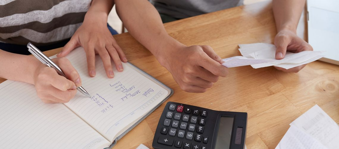 Close-up shot of unrecognizable family gathered together at wooden table and keeping records of expenses, woman taking notes in notepad